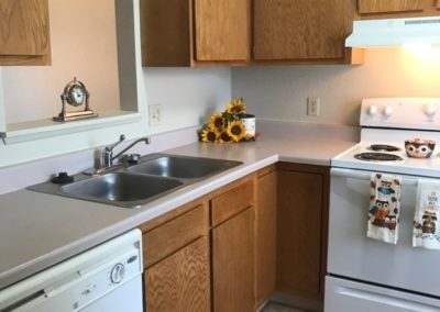 kitchen with brown cabinets, sink and white dishwasher and stove